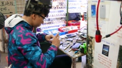 Young boy disassemble smartphone, street market repair service Stock Footage