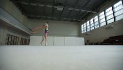 Rhythmic gymnastics: Girl training a gymnastics exercise with a hoop - stock footage