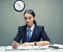 Serious business woman writing document Stock Photos