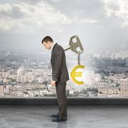 Businessman with key in back and euro sign - stock photo