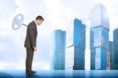 Stock Photo of Businessman with key in back and city scape