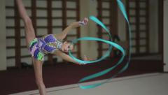 Rhythmic gymnastics: Girl training a gymnastics exercise with a ribbon Stock Footage