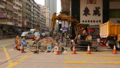 Small excavator work at lively city street, remove concrete debris to truck - stock footage