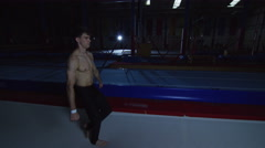 4K Professional male gymnast practicing flips on trampoline Stock Footage