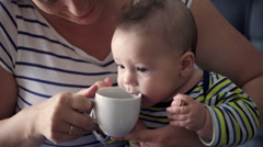 Cute small baby sitting on the mother's knees and playing with mug HD Stock Footage