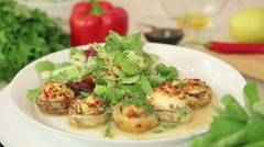 Stuffed champignon on white plate with salad Stock Footage