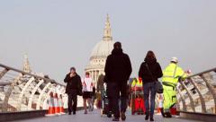 Pedestrians and runner cross Millennium Bridge towards St Pauls - stock footage