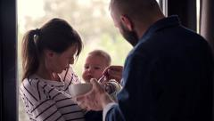 Young couple feeding baby at home HD Stock Footage
