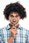 Afro american man holding magnifying glass - stock photo