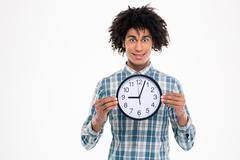 Happy afro american man holding wall clock Stock Photos