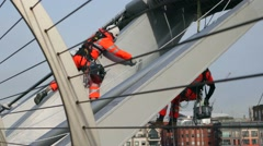 Workmen in harnesses painting the Millennium Bridge Stock Footage