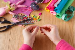 Female hands doing crafts from felt Stock Photos