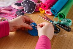 Female hands doing crafts from felt - stock photo