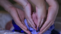 Family, hands clutching the baby legs make a figure in the shape of a heart. Stock Footage