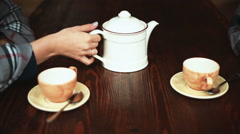 Girl hands pour tea from a teapot Stock Footage