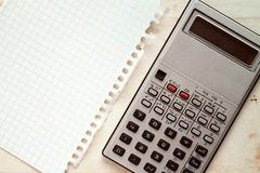 Old calculator and blank square paper - stock photo