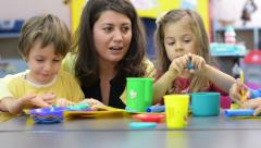 Kids playing with plasticine at kindergarten Stock Footage