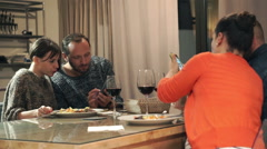 Group of friends looking at smartphones during dinner at homeHD Stock Footage