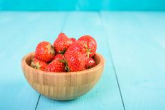 Strawberry Wood Bowl On Blue Boards - stock photo