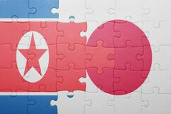 puzzle with the national flag of japan and north korea - stock photo