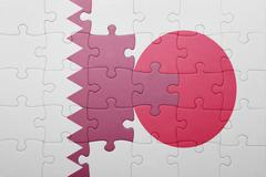 puzzle with the national flag of japan and qatar - stock photo