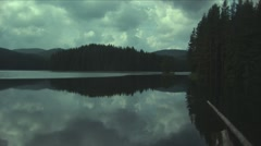 Mountain lake with tall pines and mirrored in the water Stock Footage
