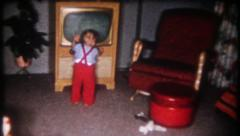 2822 - toddler adjusts the television set at home - vintage film home movie Stock Footage