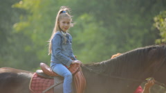 The child on the nature, riding on a horse. The baby girl on horseback. - stock footage