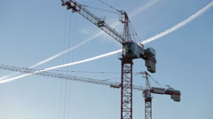 Two tower cranes working on a blue sky background. Stock Footage