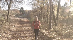 Stock Video Footage of Lady walks on the forest path at sunny autumn day