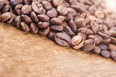 coffee grains on wooden background. light effect in the corner - stock photo