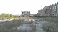 Large yard with high dry grass, complex of abandoned ruined old factory building Stock Footage