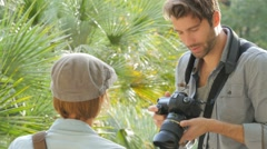 Photographer taking picture of trendy model in park Stock Footage
