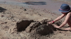 One Caucasian small girl builds sand fortress at the sandy beach. The Red Sea Stock Footage