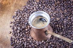 Coffee beans, vintage copper coffee pot closeup, cezve or ibrik Stock Photos