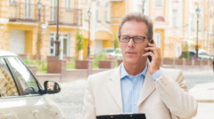 Businessperson beside his car talking on the phone - stock footage