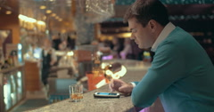 Man using cell and having alcohol drink in the bar - stock footage