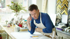 4K Cheerful business owner makes a phone call behind the counter of his shop - stock footage