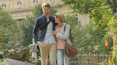 Romantic trendy couple walking in public park Stock Footage