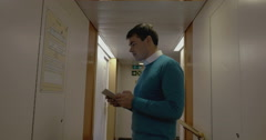 Man working with pad in hotel hallway Stock Footage