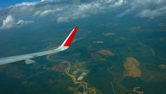 Stock Video Footage of Airborne View of an Airplane Wing Descending and Banking through Clouds