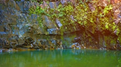 Water Trickling Slowly down a Rocky Cliff into a Pool, with Sound Stock Footage