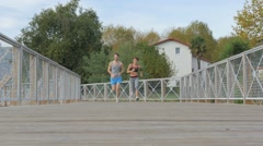 Couple of joggers running fast on bridge Stock Footage