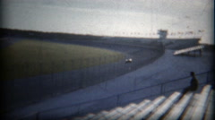 1960: Single racecar time trial race across empty grandstand crowd. Stock Footage