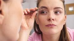 Woman tweezing eyebrows plucking with tweezers 4K Stock Footage
