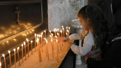 A child lights candles during Celebration of St. George the Dragon Slayer Day Stock Footage