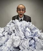 Surprised businessman reaches out from crumpled papers Stock Photos