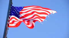 USA flag billows in wind on blue sky background - stock footage