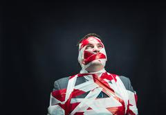 Man with stripped duct tape over body - stock photo