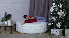 Teenager talking mobile phone, with a xmas tree - stock footage